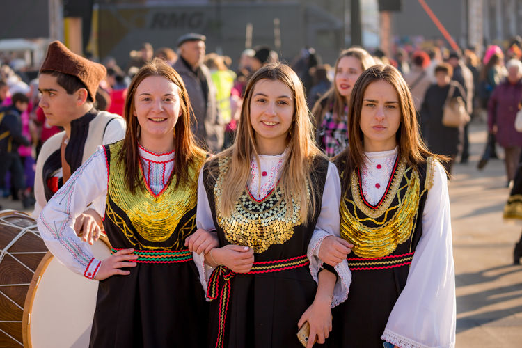 PERNIK, BULGARIA - JANUARY 26, 2018: Three girls dancers in Bulgarian folklore costumes pose for the camera in the sunny winter day at the annual International Festival of Masquerade Games Surva Event Games Kukeri Kukeri, Bulgaria Adult Arts Culture And Entertainment Day Festival Focus On Foreground Incidental People Large Group Of People Lifestyles Masquerade Outdoors People Real People Standing Surva Togetherness Young Adult