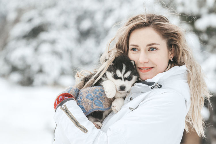 Portrait of smiling woman with snow during winter