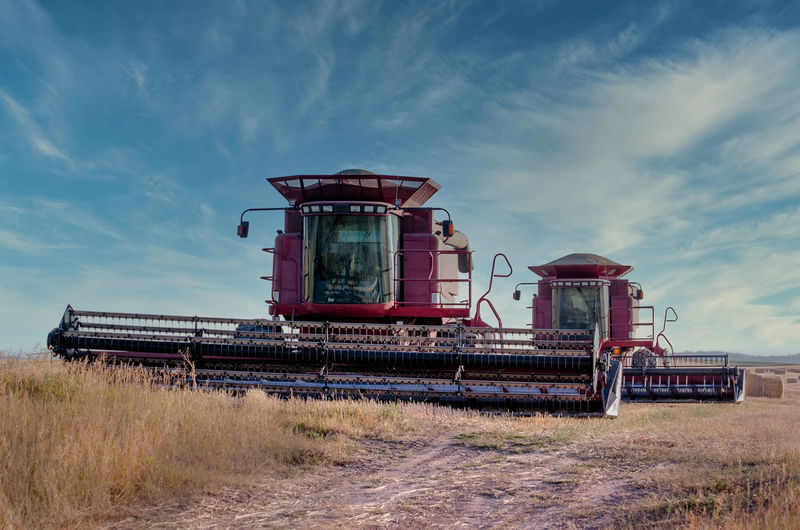 Large machines bale straw for animals in a golden idaho field in the usa