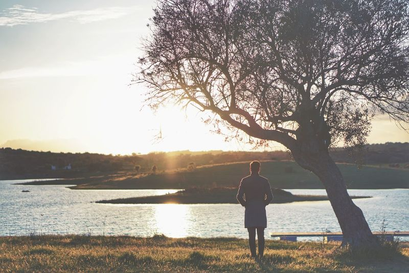 Rear View Of Man Standing By River Against Sky During Sunset