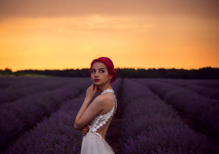 Side view of female model looking up while standing at lavender field during sunset