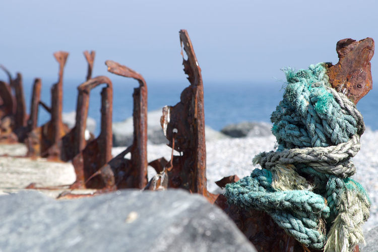 Close-up of rope tied on rusty metal against sea
