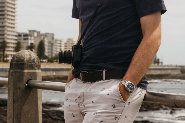 Midsection of man with hands in pockets leaning on railing