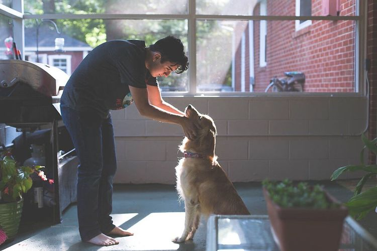 Woman with dog standing at home