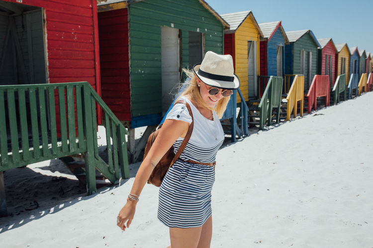 Woman standing at beach against colorful huts and clear blue sky during sunny day