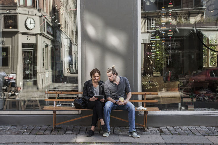 Young couple sitting on seat in city