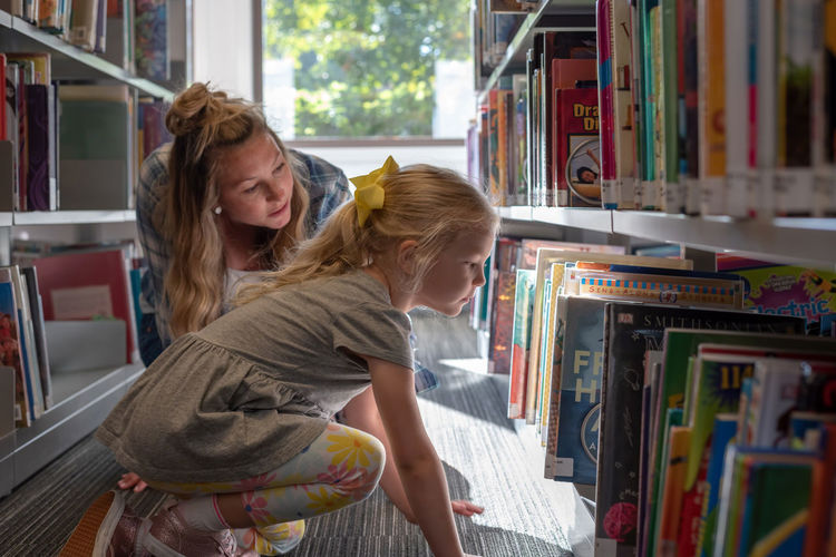 Mother with daughter choosing book in store