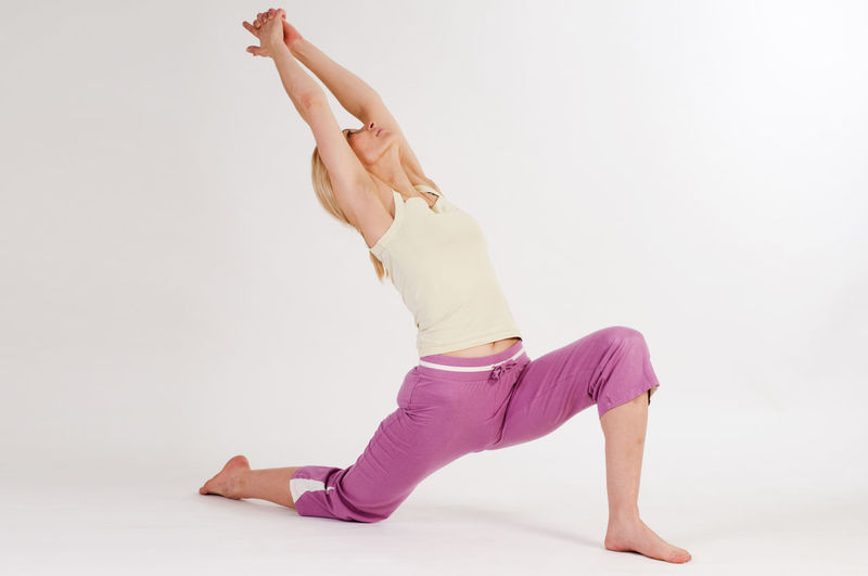 Full length of young woman practicing yoga against white background