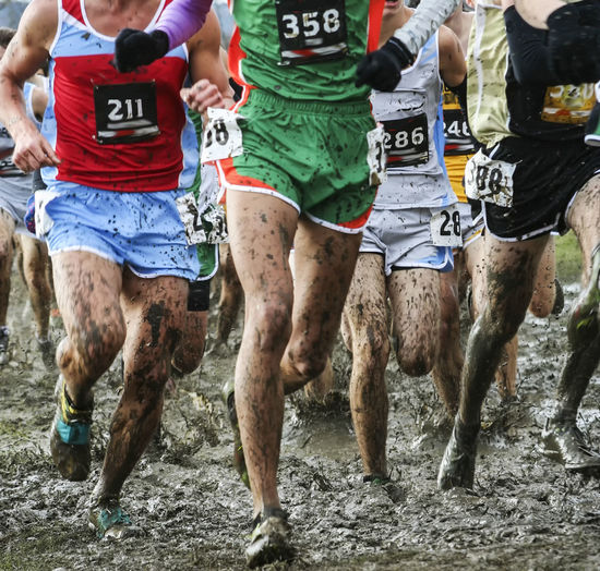 Runners racing a high school championship 5k in heavy mud with their spikes taped on with duct tape.