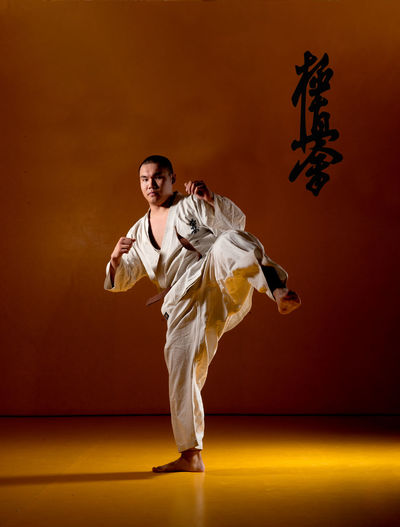 Asian man practicing karate kyokushinkai. Asian  Fight Martial Arts Arms Raised Clothing Colored Background Front View Full Length Indoors  Karate Karate Kyokushinkai Leg Martial Arts Men Motion One Person Skill  Sport Stage Stage - Performance Space Standing Standing On One Leg Studio Shot Young Adult Young Men