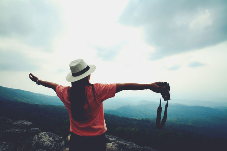 Girl wearing a white hat holding a camera Journey, Pilgrimage Trip , Traveling Beauty In Nature Clothing Cloud - Sky Day Freedom Hat Itinerary Leisure Activity Lifestyles Looking At View Mountain Nature Non-urban Scene Outdoors Real People Rear View Rock - Object Scenics - Nature Sky Solid Standing