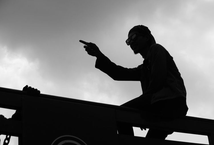 Low angle view of silhouette man pointing while sitting on metal against sky