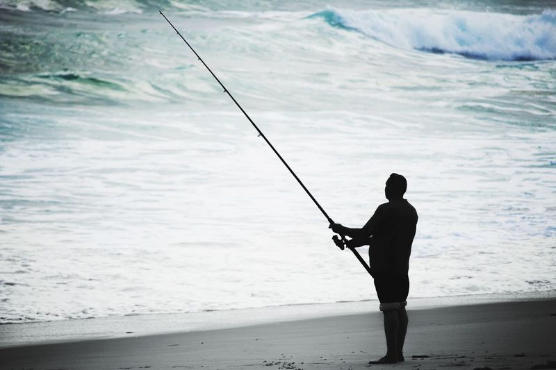 Silhouette Man Fishing On Beach