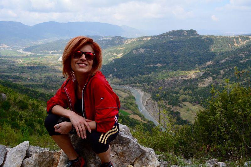 Portrait of smiling young woman against landscape