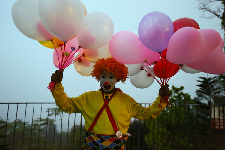 Clown holding multi colored balloons against sky