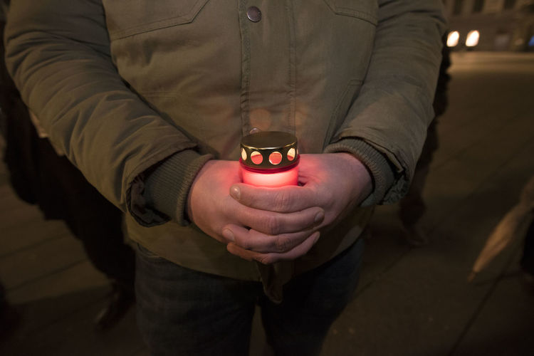 Midsection of man holding illuminated lighting equipment