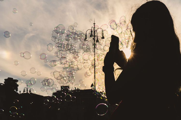 Bubble Real People Silhouette Lifestyles Bubble Wand One Person Leisure Activity Sky Nature Women Holding Fragility Blowing Vulnerability  Headshot Sunlight Men Adult Rear View Outdoors