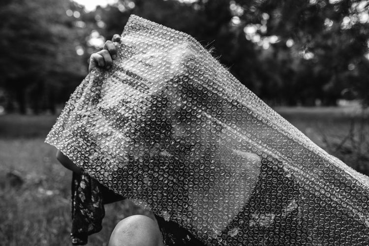 Woman Holding Bubble Wrap Plastic Foil At Park