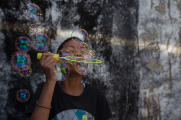 Boy blowing bubbles against wall