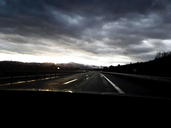 Highway against sky seen through car windshield