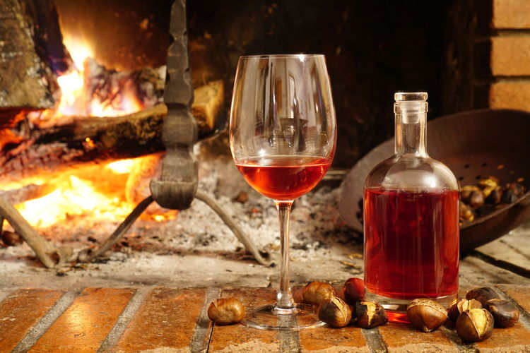 Close-up of red wine and chestnuts by fireplace at home