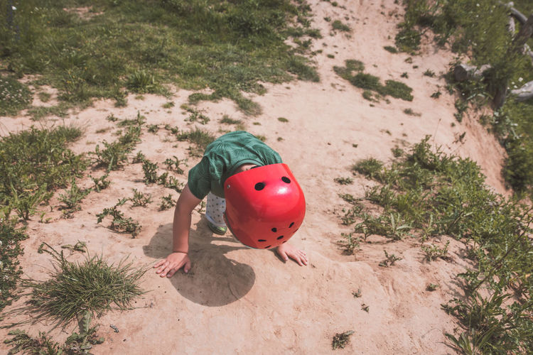 Child Childhood Climbing Day Full Length Helmet High Angle View Hill Innocence Kid Land Lifestyles Nature One Person Outdoors Plant Real People Red Sand Shadow Sunlight Toy