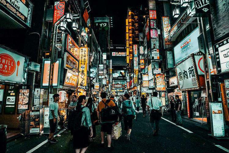 Japan Japanese Culture Advertisement Architecture Building Exterior Built Structure City City Life City Street Communication Crowd Group Of People Illuminated Large Group Of People Men Neon Night Non-western Script Outdoors Real People Script Sign Store Sign Street Text