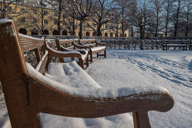Empty bench in snow covered park