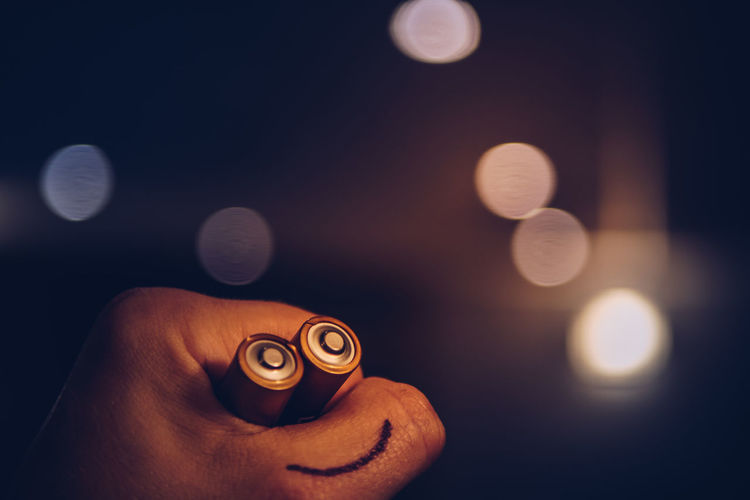 Cropped Hand Of Person Holding Batteries With Smiley Face