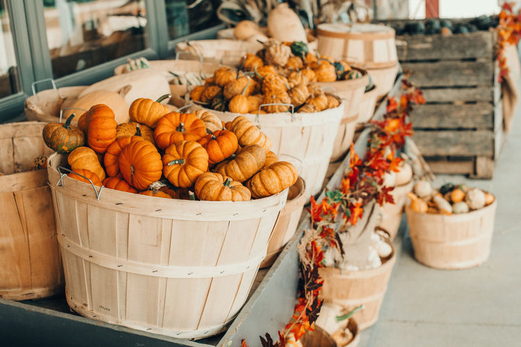 pumpkins in baskets by store on farm. autumn fall harvest. thanksgiving and halloween holiday