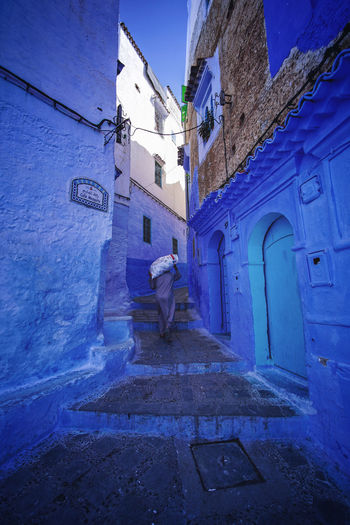 """""""The Blue City"""" We travelled from Sevilla to Tarifa, then took a ferry to Tangier, then a taxi to Chefchaouen, Morocco. EyeEmNewHere a new beginning Chefchaouen Morocco Beauty Blue City Blue Medina Architecture Building Exterior Street One Person City Lifestyles Alley Built Structure Full Length Digital Nomad Building Real People Men Walking Leisure Activity Day The Way Forward Residential District Direction Rear View Nature"""