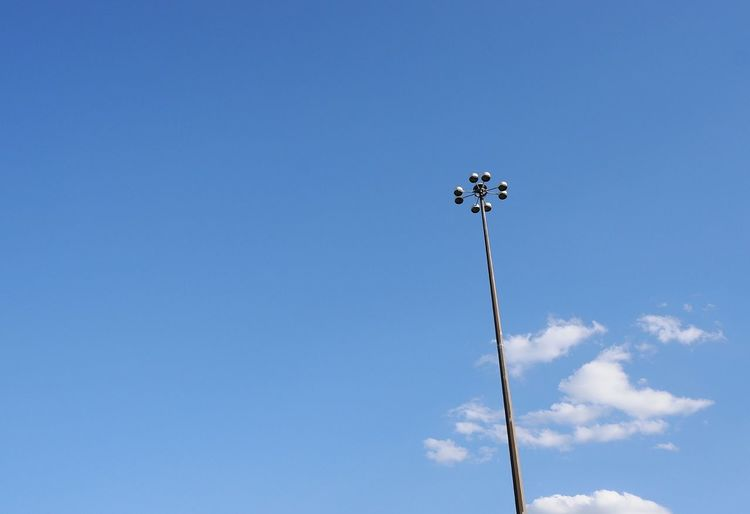 Low angle view of floodlight against blue sky