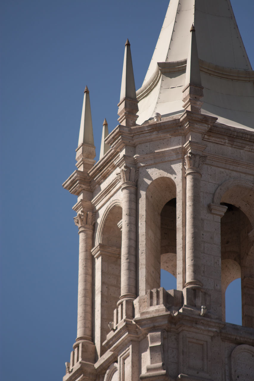 history, low angle view, architecture, no people, day, religion, built structure, outdoors, clear sky, travel destinations, spirituality, place of worship, ancient, architectural column, blue, building exterior, sky, ancient civilization
