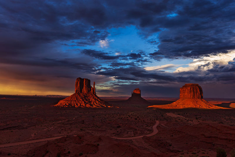Warm sunset light pours over the famous Mittens Buttes in Monument Valley, Arizona. Arizona Mitten Butte Monument Valley Monument Valley Tribal Park Sunlight USA America Awe Beauty In Nature Cloud - Sky Desert Dramatic Landscape Dramatic Sunset Geology Landscape Nature Rock Formation Scenics Sky Southwest  Southwestern Usa Sunset The Mittens Tranquility Travel Destinations