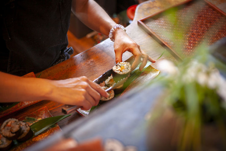 Midsection of man preparing sushi on table