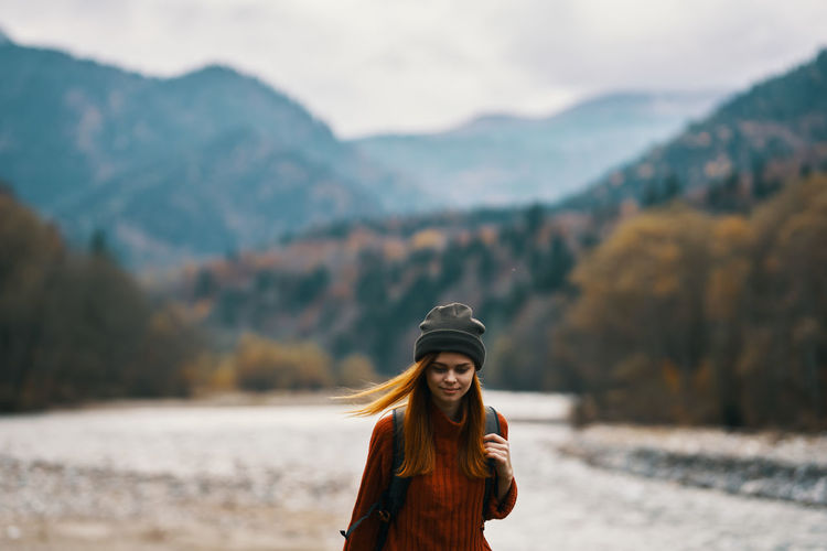 Portrait of smiling young woman standing against mountains