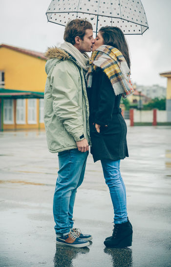 Side view of couple wearing warm clothing while kissing under umbrella in city