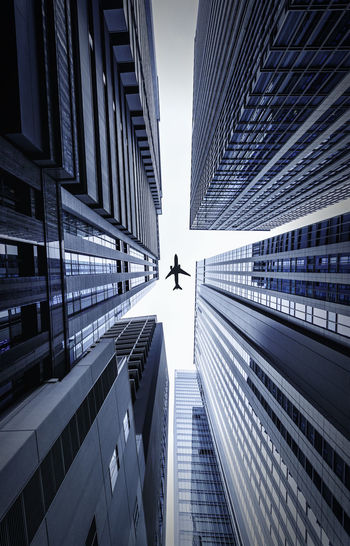 Directly below shot of modern buildings and airplane against sky