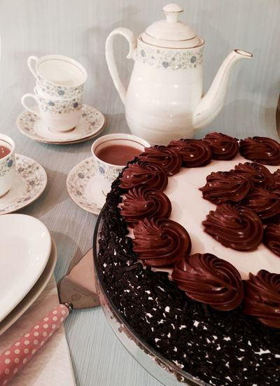 High Angle View Of Tea Cups And Chocolate Cake On Table