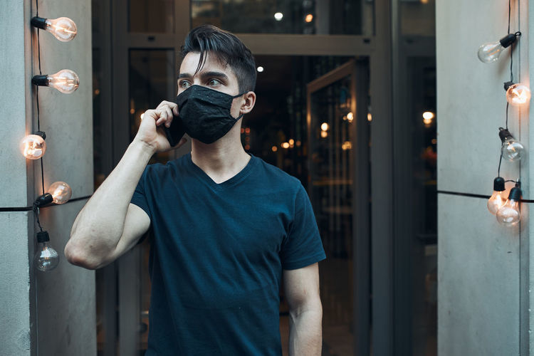 Close-up of young man wearing mask talking on mobile phone outdoors