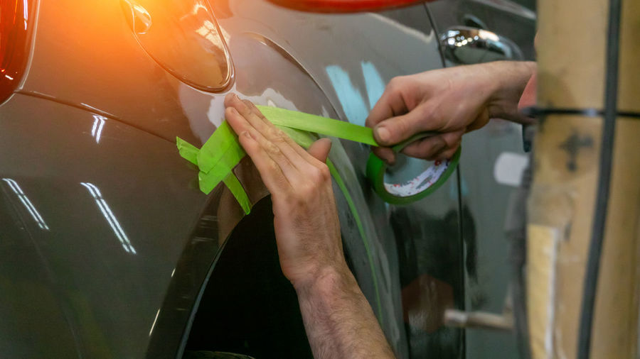 Cropped hands applying tape on car