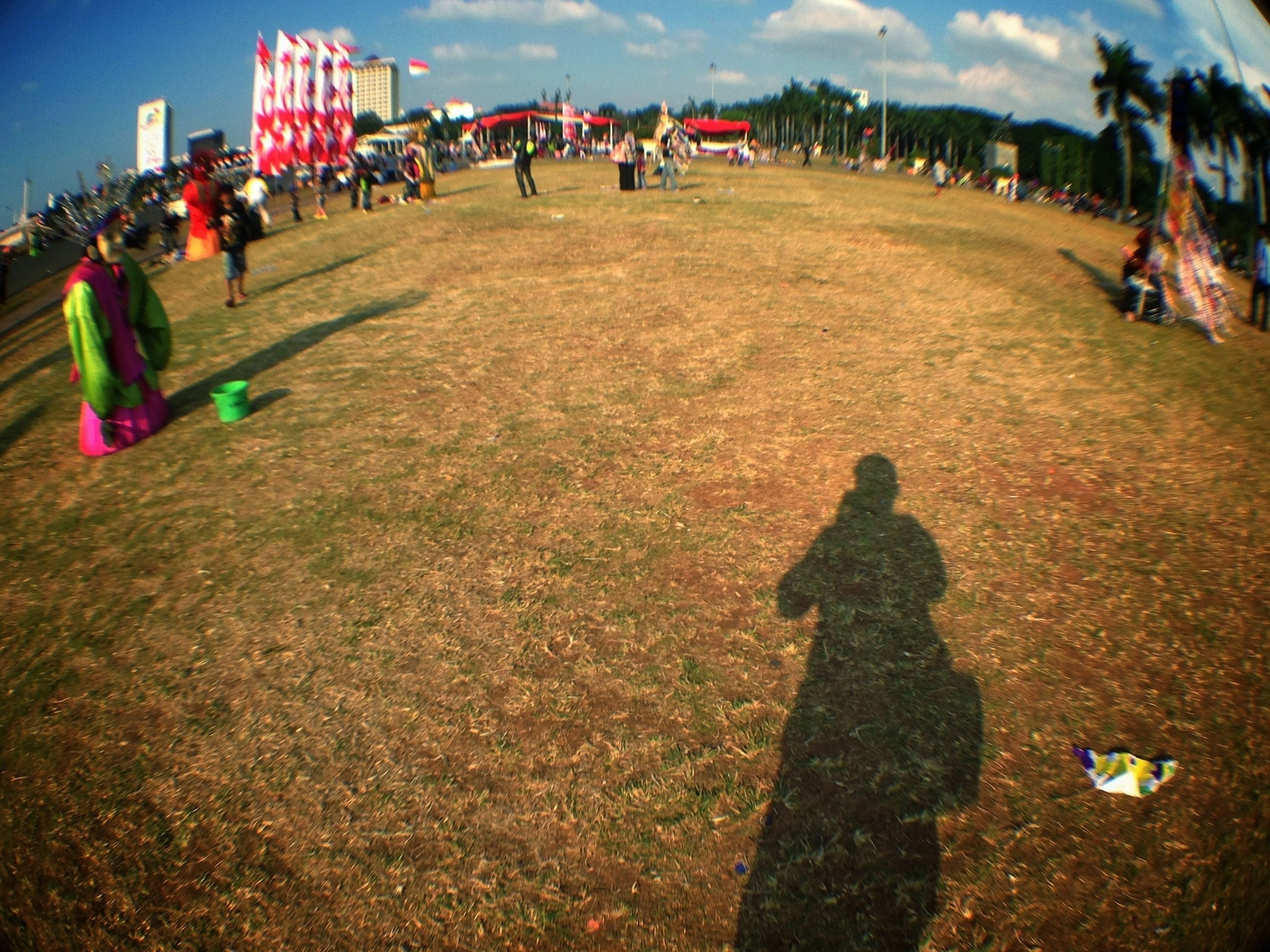 grass, men, leisure activity, large group of people, lifestyles, field, person, sky, shadow, sitting, landscape, outdoors, sunlight, day, grassy, high angle view, human representation, park - man made space, unrecognizable person