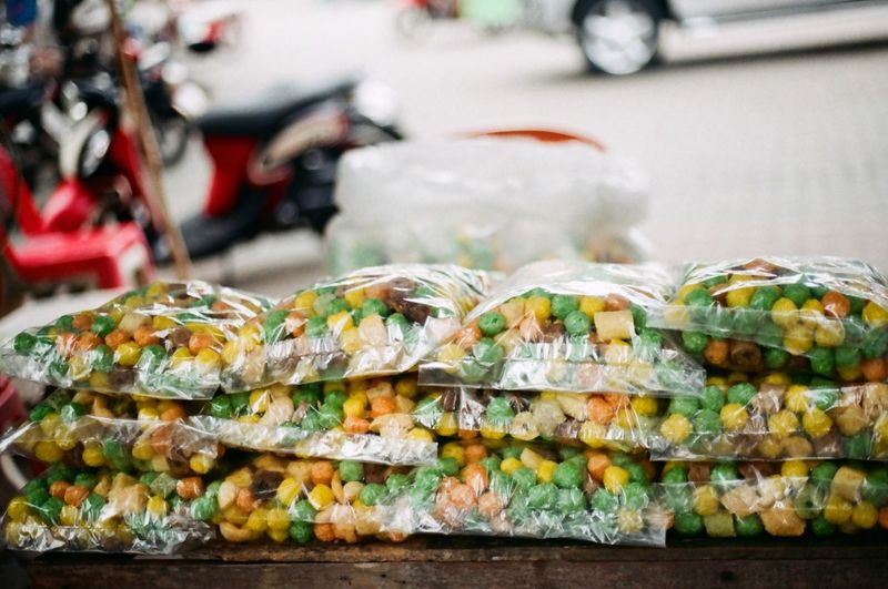 Close-up of colorful food in packets for sale at market stall