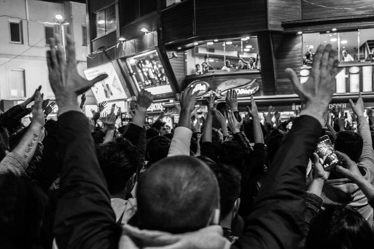 Rear view of crowd with arms raised in city at night