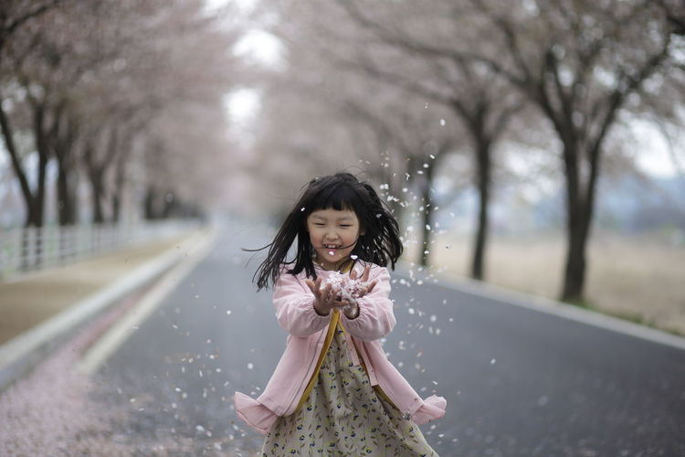 Portrait Of Cute Girl Throwing Flower Petals