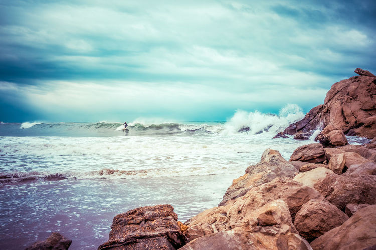 Person Surfing On Wave In Sea Against Cloudy Sky