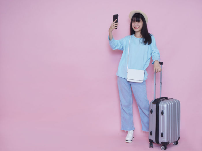 Young woman photographing with mobile phone standing against pink wall
