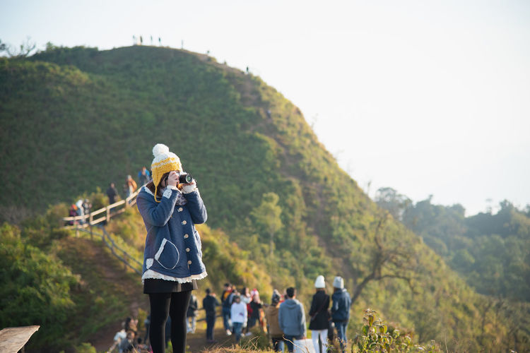 Hiker clicking picture by camera against clear sky