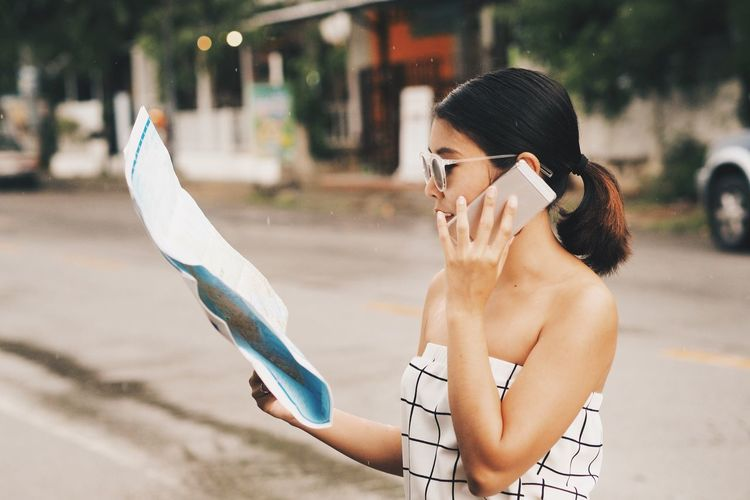 Mid adult woman with world map using phone on street