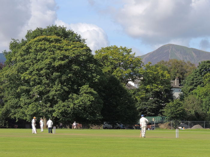 Cricket Field Beauty In Nature Cloud - Sky Cricket Match Day Field Grass Green Color Growth Leisure Activity Lifestyles Mammal Medium Group Of People Men Mountain Nature Outdoors People Playing Real People Sky Tree Women